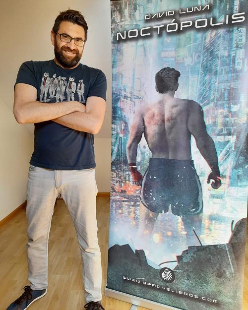 David Luna posando junto a un cartel promocional de Noctópolis